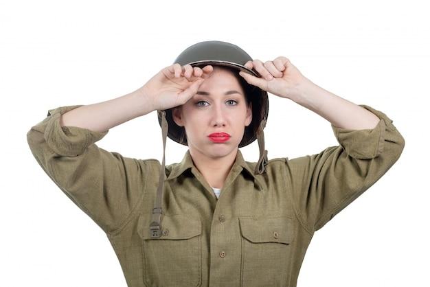 Een vermoeide mooie jonge vrouw met ww2 amerikaanse helm