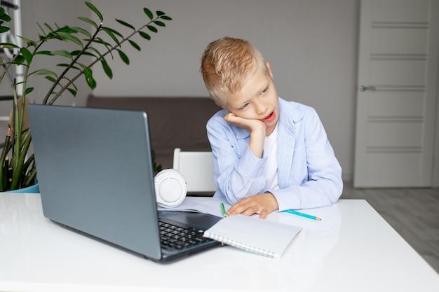 Een vermoeide schooljongen gaapt tijdens e-educatie op afstand thuis. thuisonderwijs. terug naar school