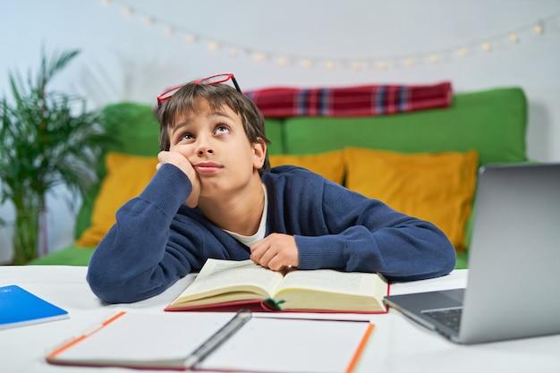 Een vermoeide studentenjongen die thuis studeert, peinzend omhoog kijkt