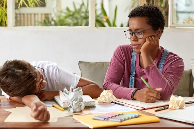 Een vermoeide tiener ligt van vermoeidheid op tafel, kan niet meer werken