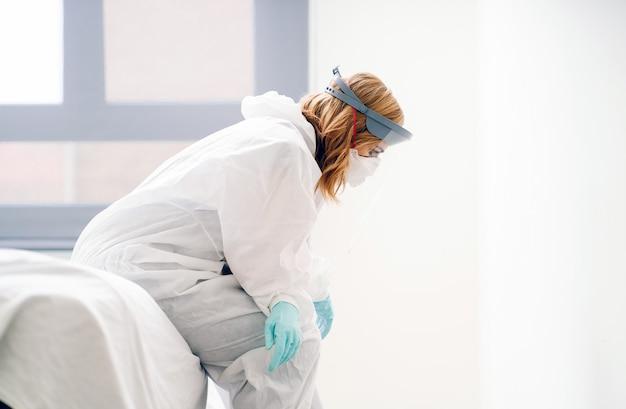 Een vermoeide vrouwelijke arts zittend op het bed in de ziekenhuis kamer