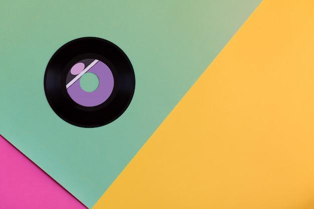 Een verouderde vinylschijf op een achtergrond van drie ton papier, popcultuur.