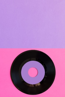 Een verouderde vinylschijf op een achtergrond van twee ton papier: roze en violet, popcultuur.