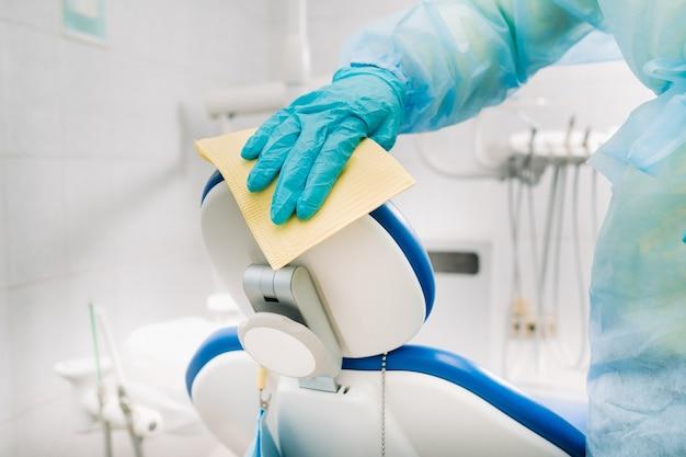Een verpleegkundige desinfecteert werkoppervlakken in de tandartspraktijk..