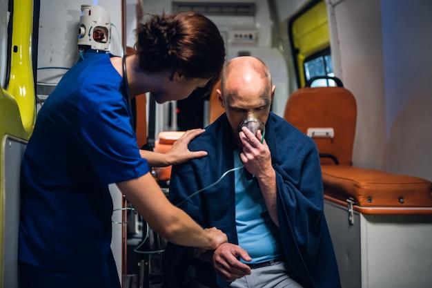 Een verpleegster die de pols van een gewonde mensenzitting in een deken in de ambulanceauto controleert