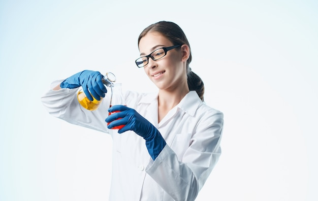 Een verpleegster in een laboratoriumjas en blauwe handschoenen met een kolf in haar hand scheikundig element laboratoriumanalyses