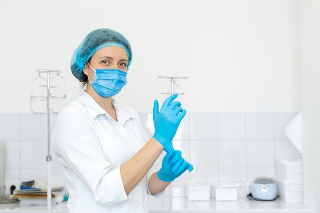 Een verpleegster in een witte jas trekt rubberen handschoenen aan voor een medische procedure in een lichte behandelkamer
