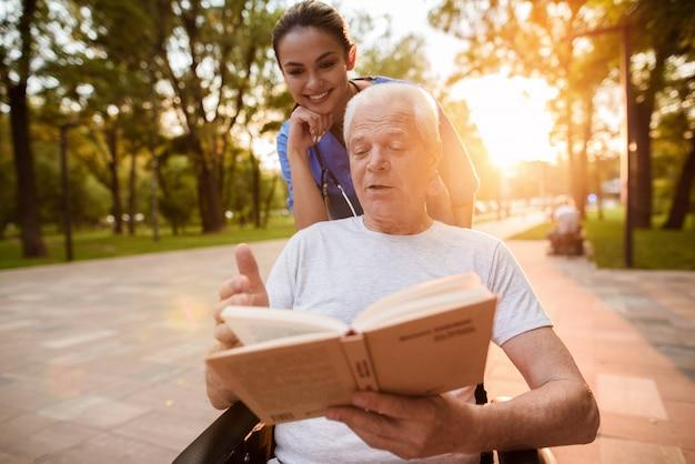 Een verpleegster kijkt toe terwijl de oude man een boek in het park leest.