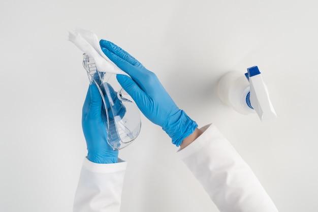 Een verpleegster met blauwe handschoenen veegt een veiligheidsbril af met een doek met een chemische oplossing om virussen en bacteriën te doden