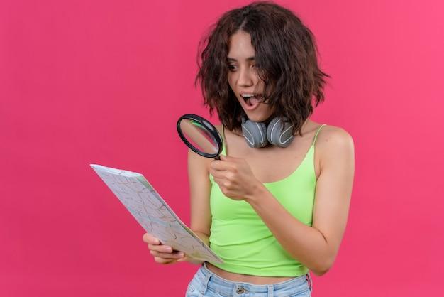 Een verrassende jonge mooie vrouw met kort haar in groene crop top in koptelefoon kijken naar een kaart met vergrootglas