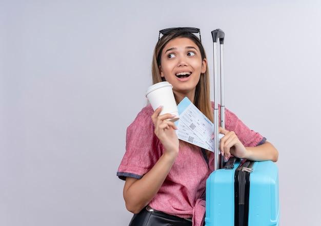Een verrassende jonge vrouw die een rood overhemd en een zonnebril draagt en opzij kijkt terwijl ze vliegtickets en een blauwe koffer vasthoudt