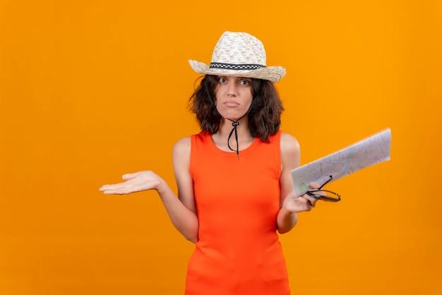 Een verrassende jonge vrouw met kort haar in een oranje overhemd met een zonnehoed en een kaart die niet weet waar ze heen moet