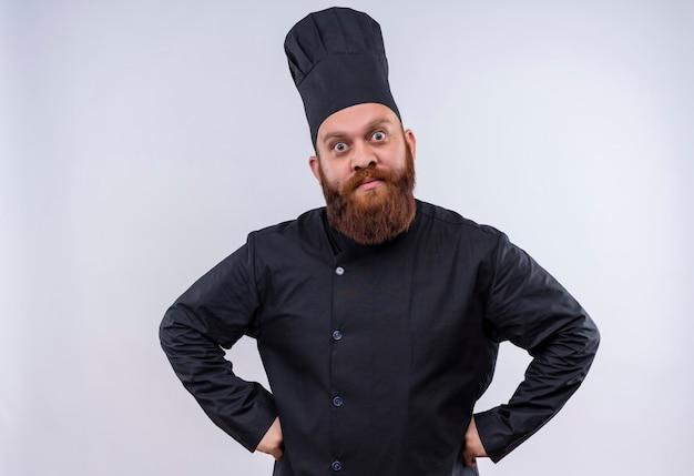 Een verrast bebaarde chef-kok man in zwart uniform camera kijken met handen op taille op een witte muur