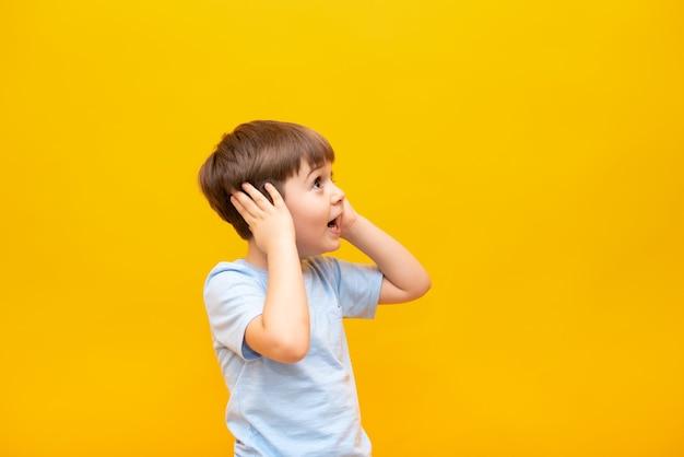 Een verrast jongetje kijkt opzij en houdt zijn hoofd vast met zijn handen. geïsoleerd op een gele muur