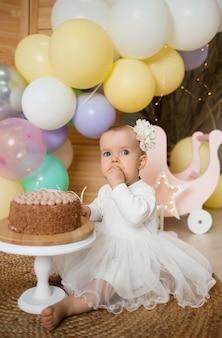 Een verrast meisje eet een cake met room op een standaard met haar handen