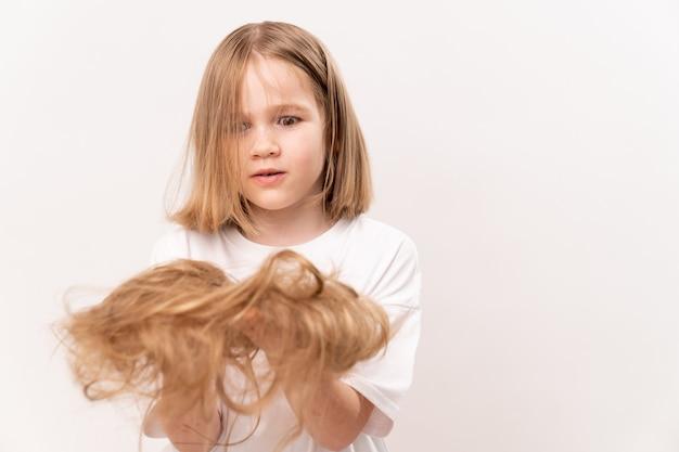 Een verrast meisje houdt in handen bijgesneden haar na het knippen op een witte achtergrond. betekent om voor het haar van kinderen te zorgen. schoonheidssalon voor kinderen.