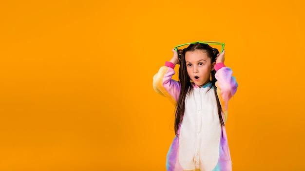 Een verrast meisje in een pluche jumpsuit en grote bril op een gele achtergrond met een plek voor tekst