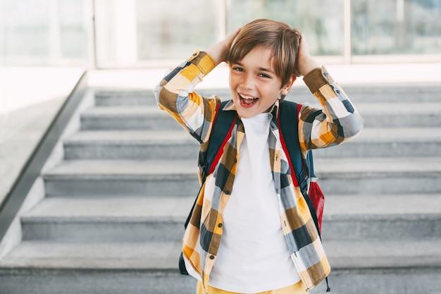 Een verraste jongen met een rugzak staat op de trap voor de ingang van de school en grimassen