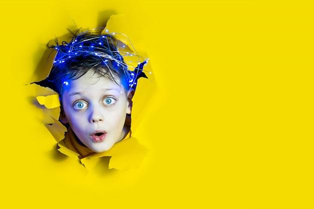 Een verraste jongen met een slinger op zijn hoofd kijkt uit een gat in de gele papieren achtergrond