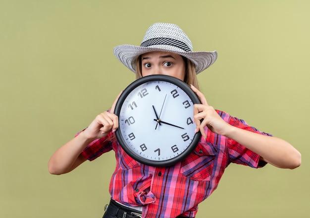 Een verraste mooie jonge vrouw in een geruit overhemd die de muurklok van de hoedenholding draagt