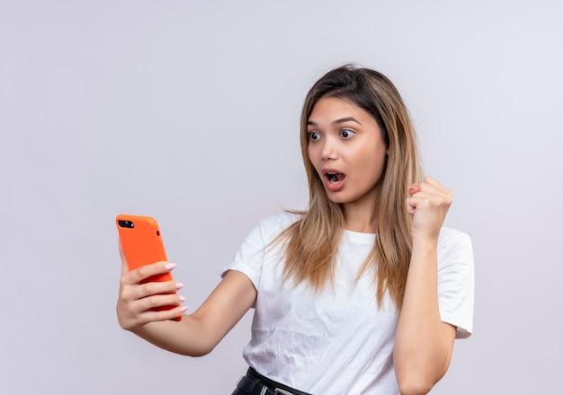 Een verraste mooie jonge vrouw in wit t-shirt die mobiele telefoon bekijkt terwijl gebalde vuist op een witte muur wordt opgeheven