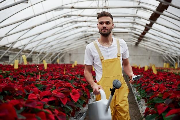 Een verre blik hebben. portret van mooie jonge kerel in de broeikas die voor bloemen zorgt.