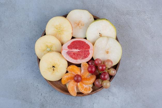 Een verrukkelijk fruit dat op een klein dienblad op marmeren achtergrond dient.