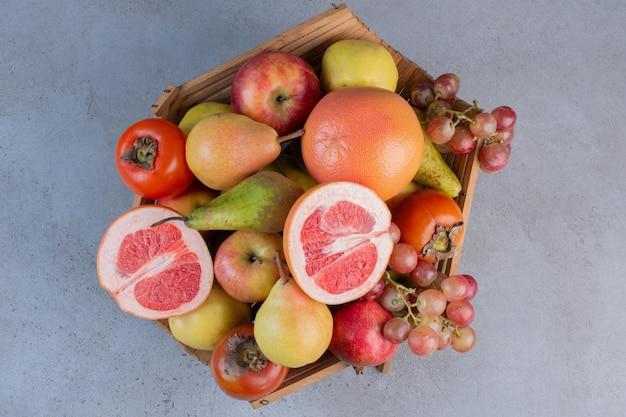 Een verrukkelijk fruitassortiment in een houten mand op marmeren achtergrond.