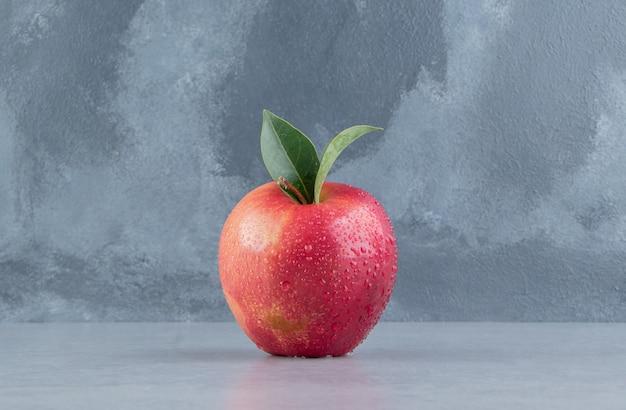 Een verrukkelijke appel weergegeven op marmer.