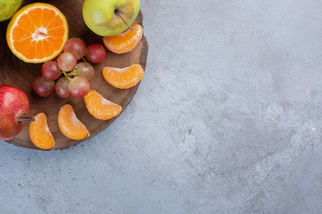 Een verrukkelijke portie fruit op een houten bord op marmeren achtergrond.