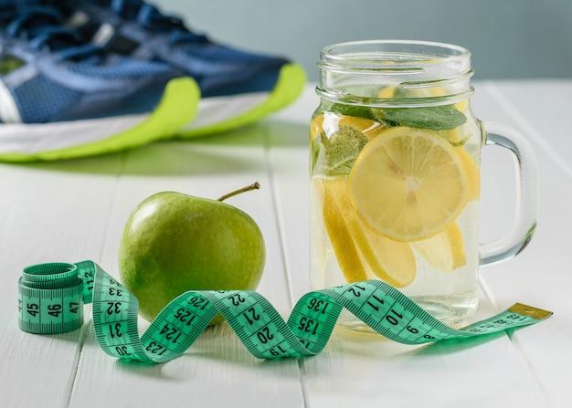 Een vers bereid drankje gemaakt van citroen en munt en appel op een witte tafel en rennen sneakers.