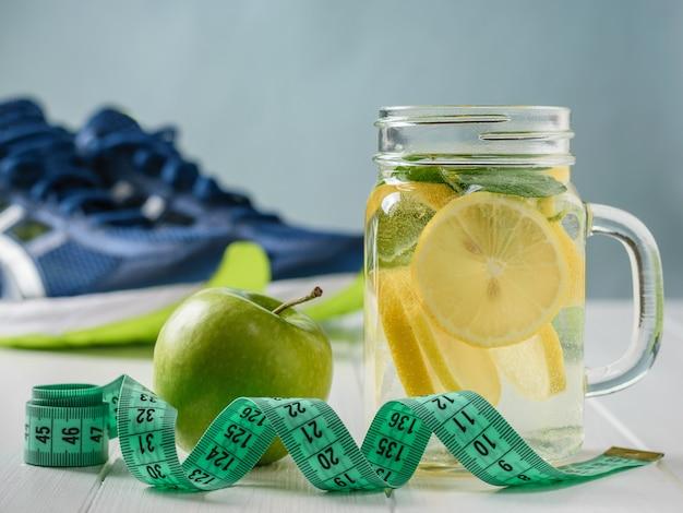 Een vers bereide drank gemaakt van citroen en munt en appel op een witte tafel en sneakers.