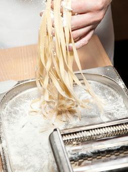 Een vers bereide portie zelfgemaakte pasta in handen van kok.
