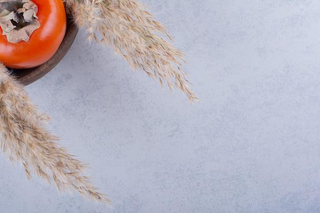 Een vers rijp persimmon fruit in houten kom.