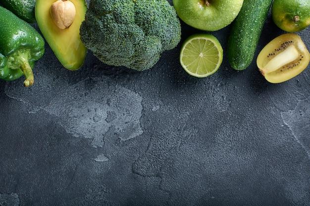 Een verscheidenheid aan gezond vers voedsel, groenten en fruit, wordt op een donkere stenen ondergrond gelegd