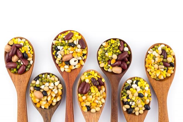 Een verscheidenheid aan gezonde graangewassen op een houten lepel op een witte grond
