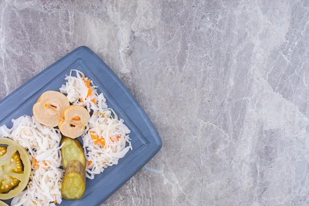 Een verscheidenheid aan ingemaakte groenten op een houten dienblad, op het marmer.