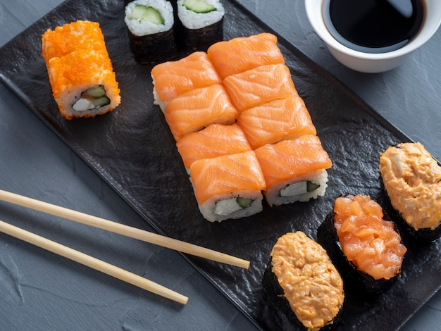 Een verscheidenheid aan japanse broodjes en sushi op een getextureerde plaat. zijaanzicht. bamboestokken van gember en saus in de buurt.