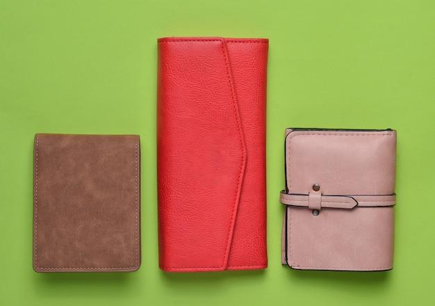 Een verscheidenheid aan leren portemonnees voor dames op een groene pastel achtergrond, damesaccessoires, bovenaanzicht, minimalisme