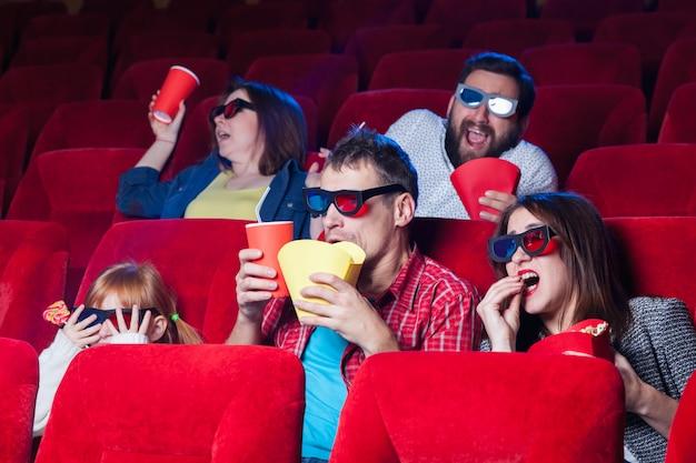 Een verscheidenheid aan menselijke emoties van vrienden met een cola en popcorn in de bioscoop.