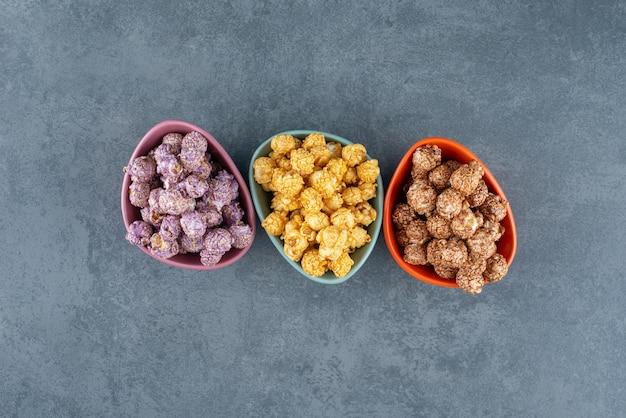 Een verscheidenheid aan popcorn-snoepkleuren, gesorteerd in kleine schaaltjes op marmer