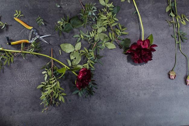 Een verscheidenheid aan prachtige bloemen liggend op een grijze tafel.