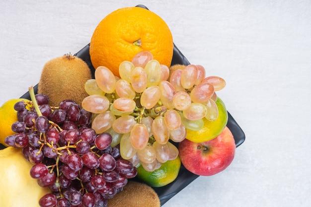 Een verscheidenheid aan smakelijke vruchten op een zwarte schaal, op het marmer.