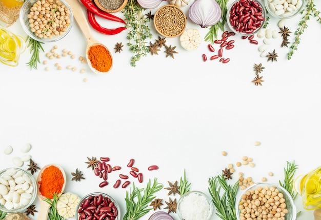 Een verscheidenheid aan specerijen en kruiden op een lichte tafel. koken tafel. uitzicht van boven. ingrediënten voor het koken. tafel tafel menu.