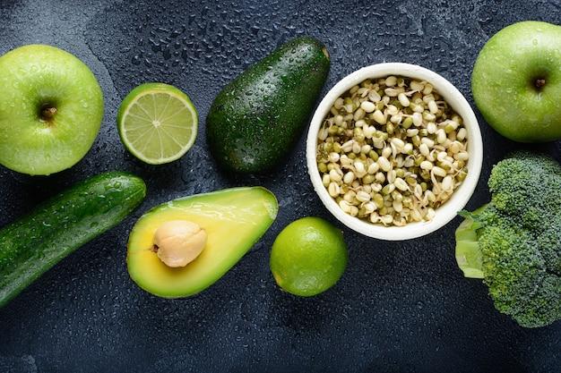 Een verscheidenheid aan verse groene groenten en fruit wordt met druppels water op een donkere stenen ondergrond neergelegd