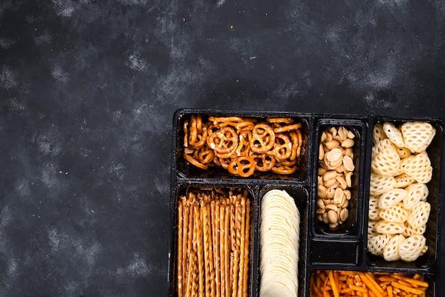 Een verscheidenheid van snacks op de doos voor bier op een concrete zwarte lijst