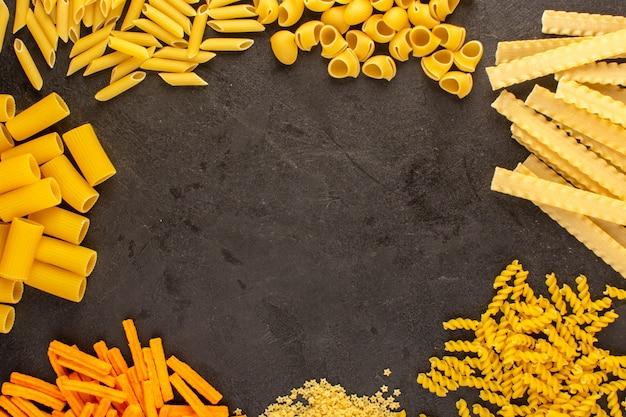 Een verschillende bovenaanzicht gele rauwe pasta vormde geïsoleerd weinig en lang op de donkere spaghetti van italiaans van het achtergrondmaaltijdvoedsel