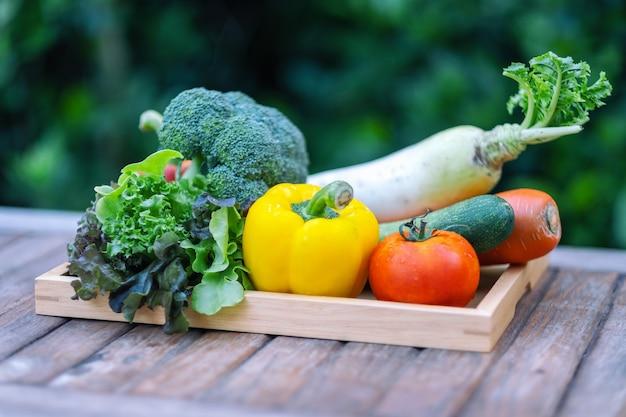 Een verse gemengde groenten in een houten dienblad op tafel