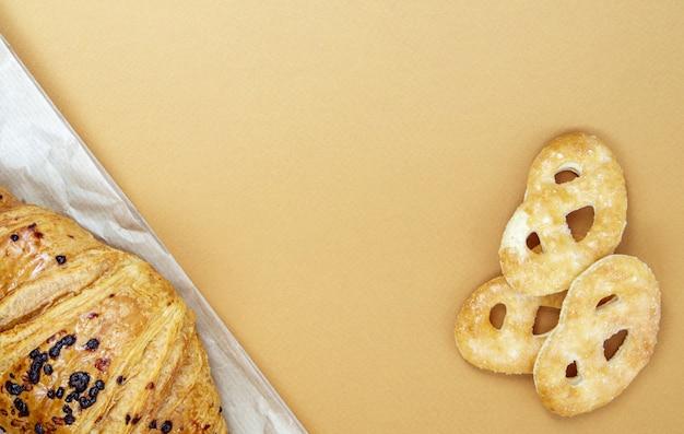 Een verse knapperige croissant met chocoladevulling en koekjes op een bruine of koffieachtergrond met kopieerruimte. klassiek traditioneel vers gebakken frans dessert, gebakjes. bovenaanzicht, plat gelegd.