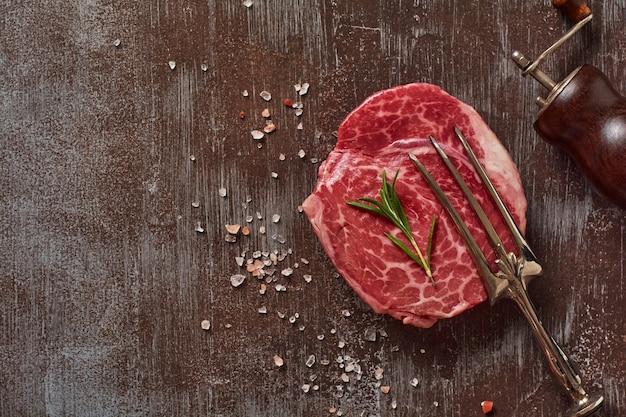 Een verse parisienne rauwe steak op wit perkamentpapier met zout, peper en rozemarijn in een rustieke stijl op oude stenen achtergrond. zwarte angus. bovenaanzicht.